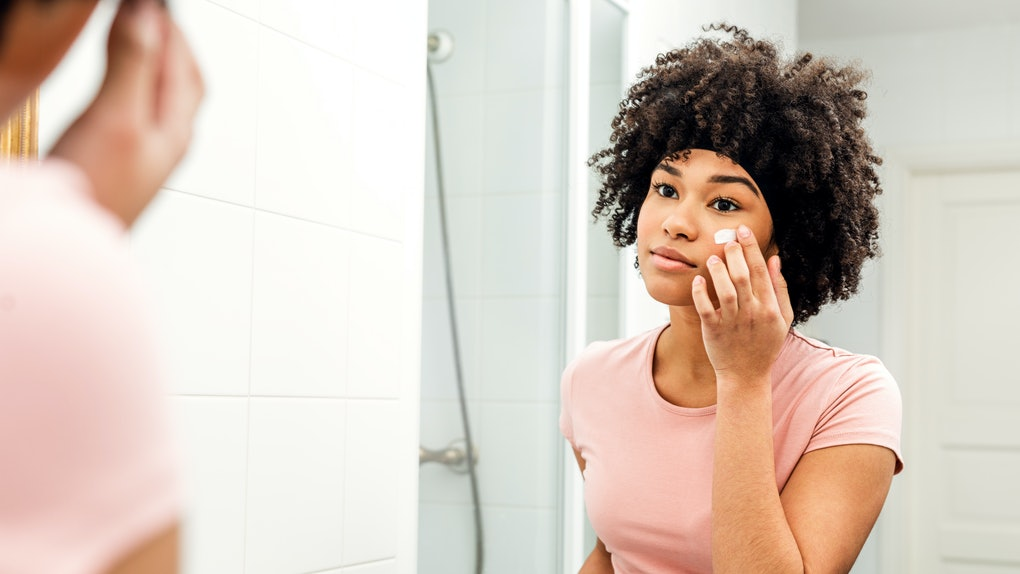 Young woman in bathroom looking in to the mirror and applying cream