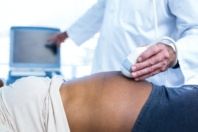 Doctor performing ultrasound on pregnant woman in hospital