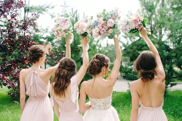 Wedding bouquets. Bridesmaid's bouquets. Bride with bridesmaids in dust pink dresses have fun in wedding day. Happy marriage and wedding party concept.