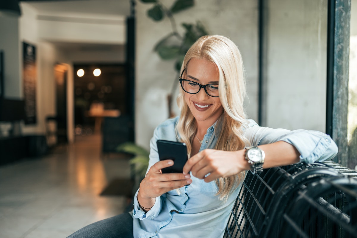 Close-up image of gorgeous blonde woman texting indoors.
