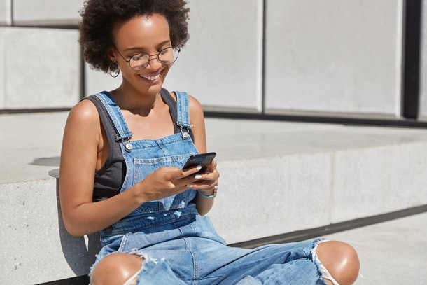 Happy fashionable feminine blogger sits crossed legs outside, texts message for post on personal website, being in good mood, sends feedback, wears stylish outfit for youth, enjoys recreation time