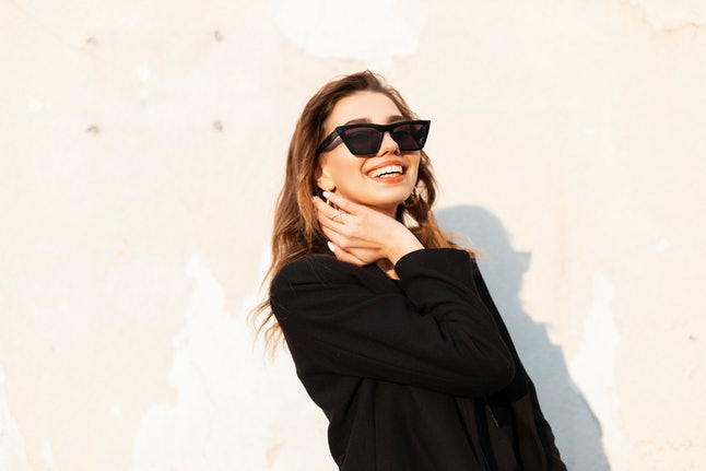 Pretty positive young hipster woman in black elegant coat in dark trendy sunglasses stands and smiles near white wall outdoors in the city. Funny joyful girl enjoys orange bright sunshine. Happy day.