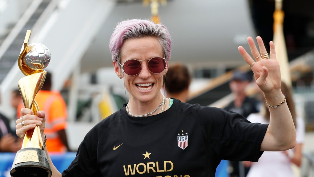 Megan Rapinoe holds the Women's World Cup trophy mafter she and other embers of the U.S. soccer team, winners of a fourth Women's World Cup, arrived at Newark Liberty International Airport, in Newark, N.J