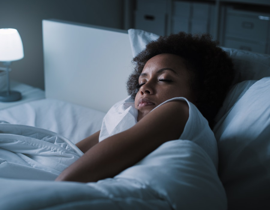 Young woman sleeping in her bed at night, she is resting with eyes closed