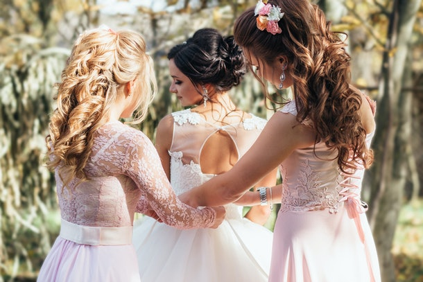 Bridesmaids help bride to put on a wedding dress outside