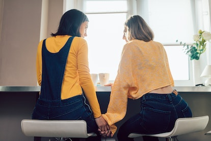 two lesbians having a snack in the morning. back view photo. relationship, love concept. serious conversation between close , true friends
