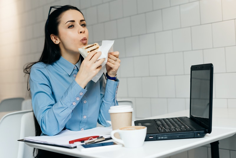 hungry business woman sitting in the office at the table and eating