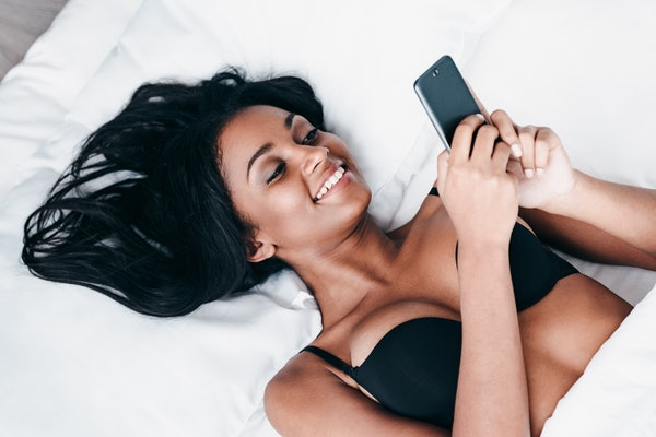 Great morning message. Top view of beautiful young African woman in black lingerie lying in bed and using her smart phone