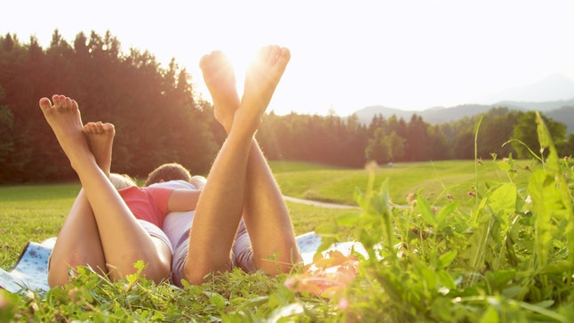 LENS FLARE CLOSE UP: Happy woman and her boyfriend enjoy a fun date in the countryside and lie on a blanket in the middle of an empty meadow. Adorable couple lying in the idyllic nature on a sunny day