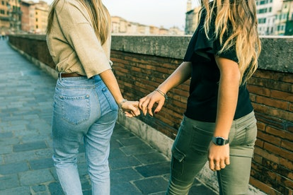 Girls best friends holding hands and walking. Rear view of two teenage girls walking together on the pavement in the city. Friendship and lifestyle concepts.