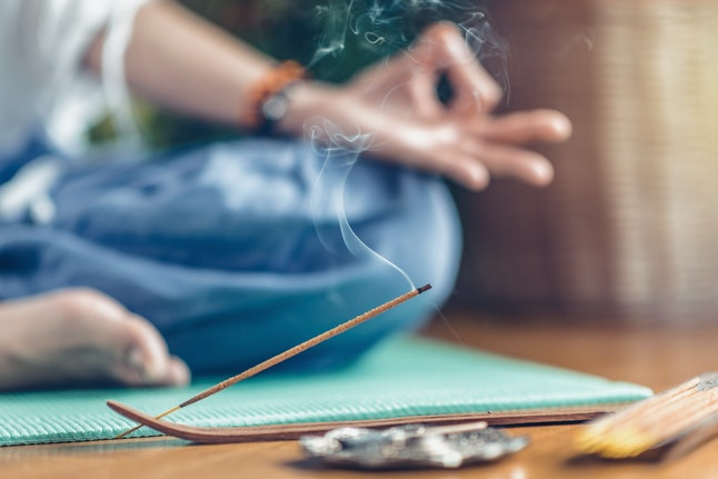 Woman meditating in lotus position on turquoise yoga mat on wooden floor. Focus on incense stick and smoke. Unrecognizable yoga practitioner in the background. Relax after Yoga training