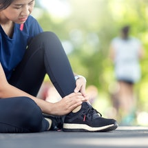 Young asian woman suffering ankle injury. Runner girl is injured by sprain ankle while running or exercising. Female runner touching foot in pain due to sprained ankle. Injury from workout concept