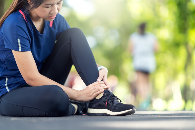 Young asian woman suffering ankle injury. Runner girl is injured by sprain ankle while running or ex...