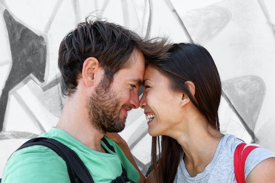 Interracial couple young happy Asian woman and Caucasian man lovers smiling laughing kissing portrai...