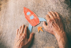 A close up of an elderly man holding a paper rocket on a wooden table. Concept of thinking about childhood dreams, sadness and loneliness.