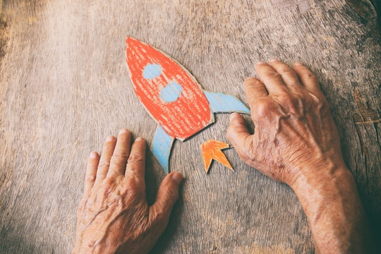 A close up of an elderly man holding a paper rocket on a wooden table. Concept of thinking about chi...