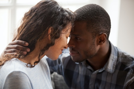 Close up of loving mixed race couple hug relaxing at home together looking in eyes, tender black man...