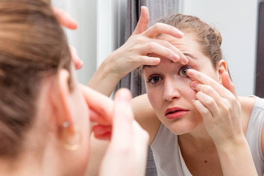 closeup of beautiful girl looking at herself leaning forward to bathroom mirror to apply or remove her contact lens, holding one eye lid, female face in a blurred foreground