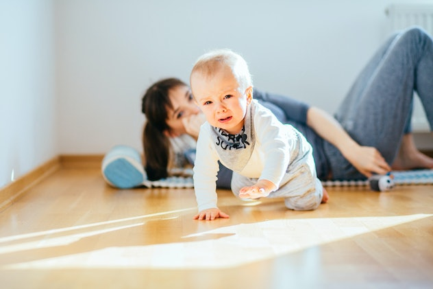 Crying infant baby boy crawling to the camera while his mother workout on mat on background behind him at home interior. Sport, motherhood and active lifestyle concept.