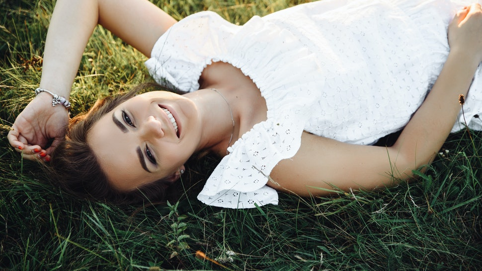 Happy smiling girl in a white summer sundress lies on the grass and looks into the camera. View from above. Top view