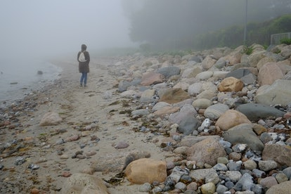 Woman in the fog on the coast