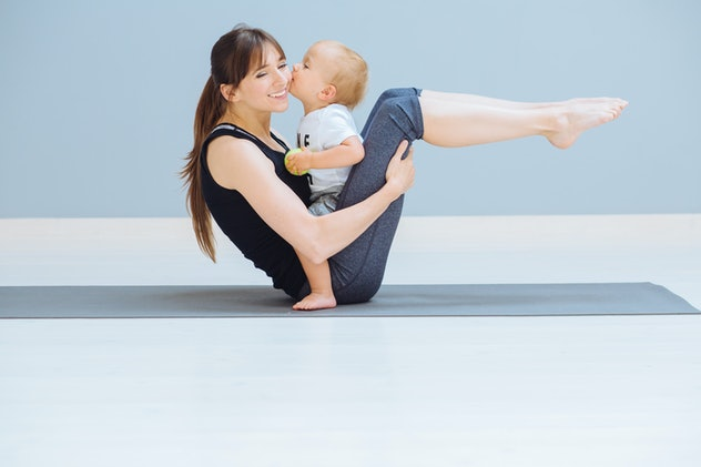 Mom swings a press and her sweet baby kissing her in cheek. A sports mother is engaged in fitness pilates exercie with toddler son at home. Child sit on mom's abdomen. Motherhood, healthy life concept