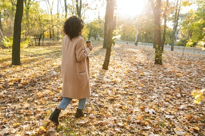 Back view photo of a beautiful young african woman walking outdoors in a spring park drinking coffee.