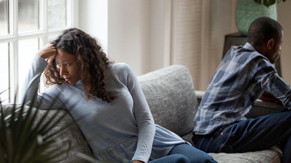 Depressed mixed race couple sit separate on couch having relationships problems, stressed upset black husband and wife avoid talking after fight, sad man and woman think of divorce or breakup