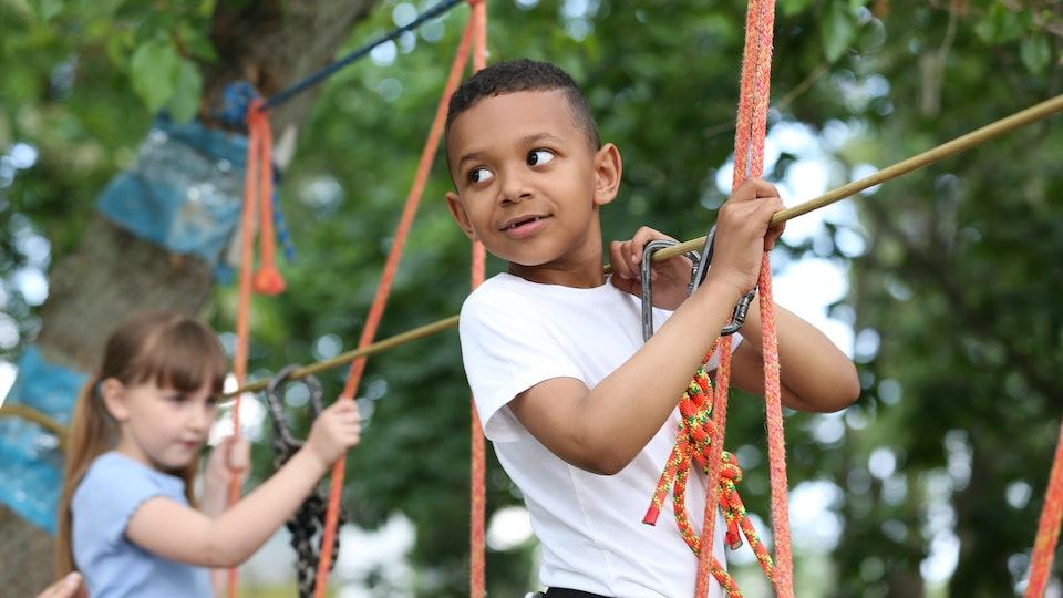 Little African-American boy climbing in adventure park. Summer camp