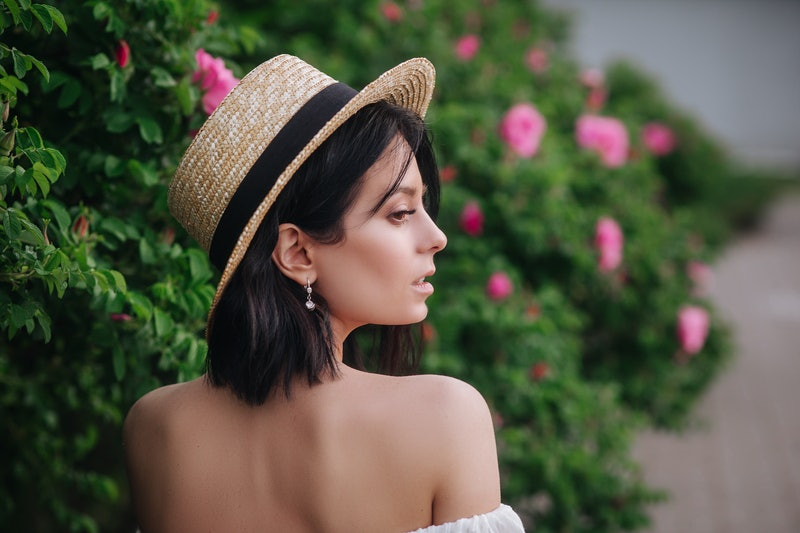 Outdoor close up portrait of young beautiful happy smiling girl wearing stylish straw hat.