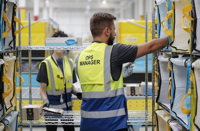 Workers sort packages in the new Amazon Sorting Warehouse in the Settecamini area of Rome, 11 July 2019. Reports state Amazon hopes to increase its logistics capacity and flexibility in Italy and ensure faster deliveries to clients. In addition the warehouse is hoped to provide better service for companies selling at Amazon as they benefit from distribution networks. The new sorting unit creates 70 new jobs and covers a space of 8000 square meters.