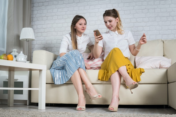 Two young girls are sitting on the couch, a friend at a party