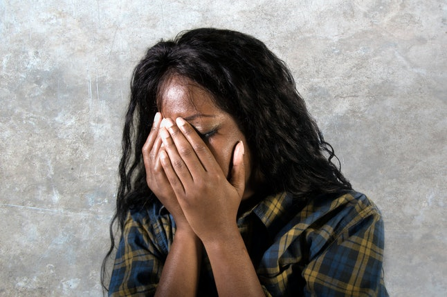 young sad and depressed black African American woman crying anxious and overwhelmed feeling sick and stressed isolated on studio background suffering depression problem and anxiety crisis