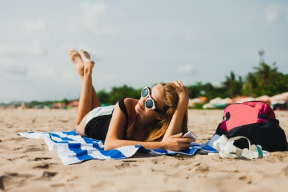 young beautiful girl lying on a towel on the beach with long hair with glasses talking on the phone, holding a modern smartphone, gadget, sunshine beach Miami, outdoor portrait, close up