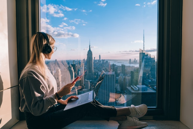 Blonde hair female blogger listening to music in headphones during freelance work on laptop computer. Hipster girl traveler enjoying panoramic view of New York downtown and studying with audio book