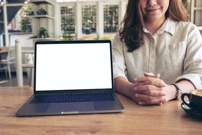 A woman presenting work with mockup laptop with blank white screen on wooden table