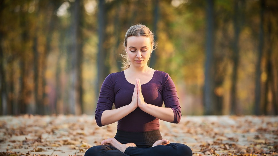 Beautiful young woman meditates in yoga asana Padmasana - Lotus pose on the wooden deck in the autumn park.