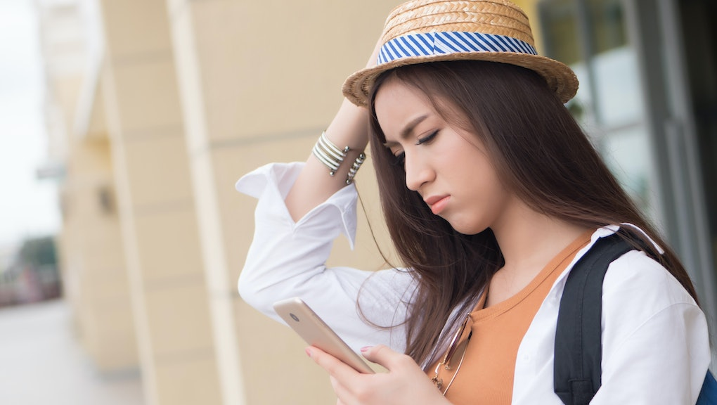 Unhappy Asian Chinese woman traveler using smart phone; portrait of unhappy sad Chinese Asian woman tourist using smartphone; communication technology, holiday, vacation, travel, tourism concept