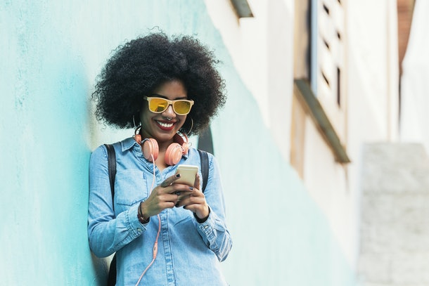 Beautiful afro american woman using mobile in the street. Communication concept.