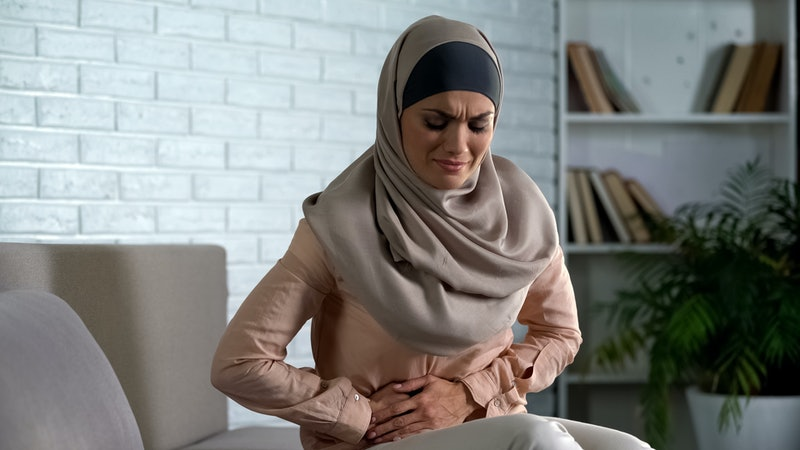 Muslim woman suffering abdominal pain, period cramp, needs medical aid