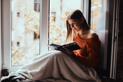 A young woman in a warm sweater covered her legs with a blanket, looking at photo album, sitting on the windowsill
