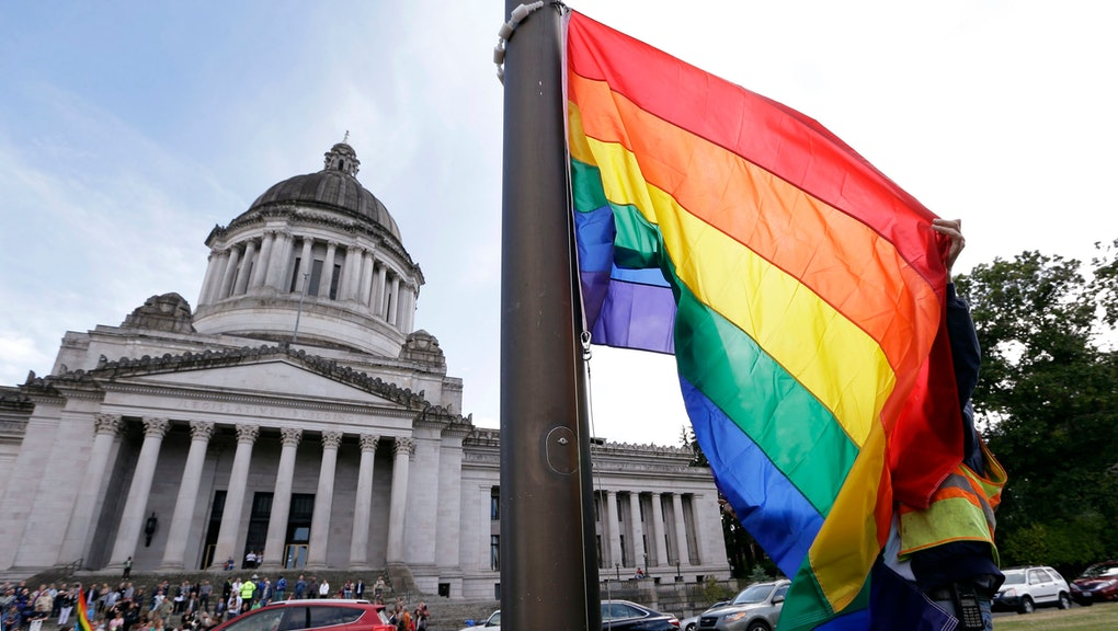 A state worker unfurls a rainbow flag in front of the Washington state Capitol to prepare it to be raised and then lowered to half-staff to mark last weekend's mass shooting at a central Florida nightclub, in Olympia, Wash. Gov. Jay Inslee and members from the LGBT community later raised the flag in honor of Gay Pride month, before it was lowered. A gunman wielding an assault-type rifle and a handgun opened fire inside Pulse, a crowded gay nightclub in Orlando, Florida, early Sunday, leaving at least 49 people dead in the worst mass shooting in modern U.S. history
