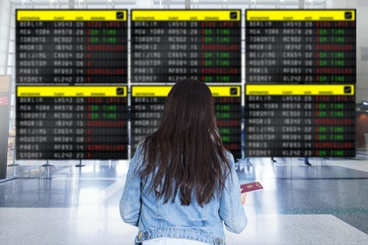 Woman traveller watching at airport billboard for her delayed flight