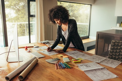 Young african businesswoman working on project. Woman working at home office, writing on a graph on a table.