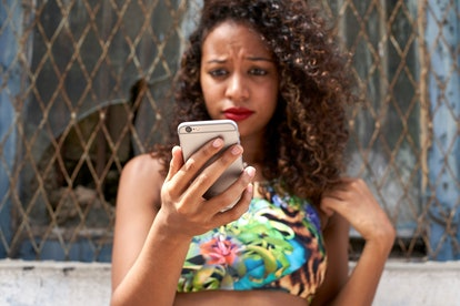 Woman frowning checking her phone