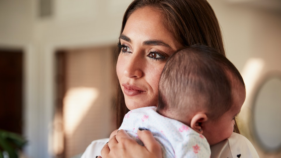 Millennial Hispanic mother holding her newborn son close to her chest, head and shoulders, close up