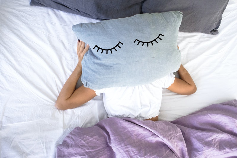 a young girl sleeping in white bed does not  want to get up early in the morning,covering her face with a pillow with closed eyes on it.