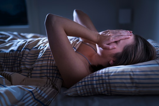 A person who is distressed is laying in bed with their hands over their face, and they are under a plaid comforter. Adults experiencing sleep terrors will often look fearful and confused with their eyes open, but they are not actually awake.