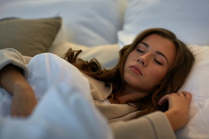 night, rest, comfort and people concept - young woman sleeping in bed at home