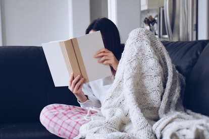 Gigi's sitting on a living room couch with a blanket and reading a book